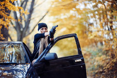 Blonde girl with weapon. Near the black car royalty free stock photos