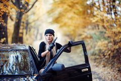 Sexy blonde girl with weapon. Near the black car Stock Photo
