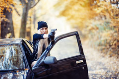 Blonde girl with weapon. Near the black car stock images