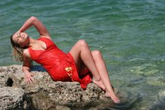 Blonde girl with wet dress. Blonde girl with wet red dress royalty free stock photography