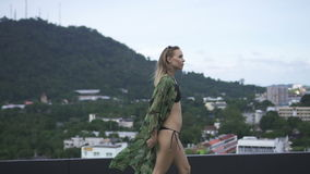 Sexy Blonde Glamour Woman Wearing Black Swimwear And Floral Long Shirt Walking On A Rooftop In