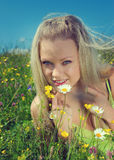 blonde on green meadow with camomile royalty free stock photo
