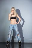 Sexy blonde in jeans and bra. On a gray background Stock Image