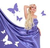 Sexy blonde jonge vrouw in blauwe zijdekleding met vlinders Stock Afbeeldingen