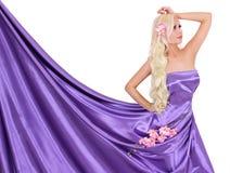 Sexy blonde junge Frau im purpurroten silk Kleid mit Blumen Stockfoto
