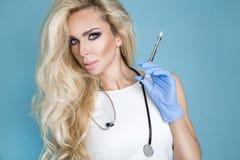 Sexy blonde Krankenschwester in den Gläsern, ein Stethoskop halten Lizenzfreie Stockfotos