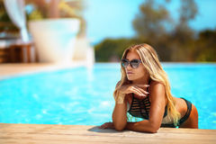 Sexy blonde lady on the beach. Sexy attractive blonde lady posing in fashionable swimsuit on the beach, sunbathing Stock Image