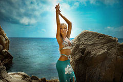 Sexy blonde lady on the beach. Sexy blonde woman posing on the rocky beach. Summer day. Blue sky Stock Images