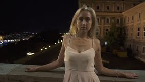 Sexy blonde lady in long elegant pink dress posing on the balcony of old marble castle at night stock video footage