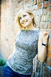 blonde lady standing near a brick wall Royalty Free Stock Image