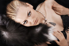 Sexy blonde laying on black just wearing fur Royalty Free Stock Photos
