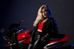 Sexy Blonde Leaning Against Motorcycle Shot Stock Photography