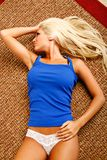 Sexy blonde look away. Beauty young woman poses on floor wearing white lace thong and tank top Stock Photo