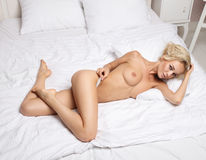 Sexy blonde lying on the white bed Stock Images