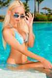 Sexy Blonde Meisjeszitting in Zwembad Stock Afbeelding