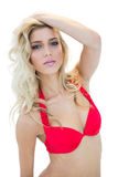 Sexy blonde model in red bikini looking mysteriously at camera Stock Photography
