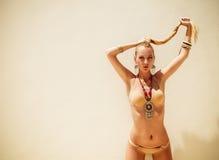 Sexy blonde moderne Frau, die in einem goldenen Bikini aufwirft Stockbild