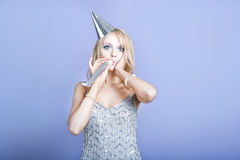 Sexy blonde party girl wearing silver dress and blowing party whistle Stock Images
