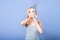 Sexy blonde party girl wearing silver dress and blowing party whistle Royalty Free Stock Images