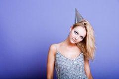 Sexy blonde party girl wearing silver dress and party hat Royalty Free Stock Photography