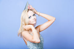 Sexy blonde party girl wearing silver dress and party hat Royalty Free Stock Photos