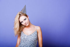 Sexy blonde party girl wearing silver dress and party hat Stock Photo