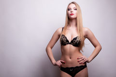 Sexy blonde with perfect body in bikini on gray background Royalty Free Stock Photo