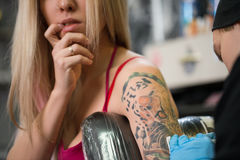 Blonde posing in tattoo studio. While a master drawing tattoo on her forearm royalty free stock images