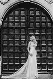 Sexy blonde Prinzessinbraut, die nahe altem Schlosstor b&w aufwirft Lizenzfreies Stockfoto