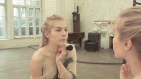 Sexy blonde Pulvertülle nahe dem großen Spiegel Eine glückliche junge Frau wird fertig, sie zu treffen geliebt stock video footage