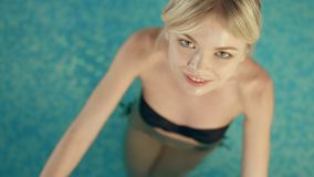 blonde relaxing in the swimming pool stock video