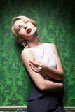 Sexy blonde on retro green wallpaper background Stock Images