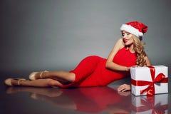 Sexy blonde Sankt in einem roten Kleid, das mit Weihnachtsgeschenk aufwirft Lizenzfreie Stockfotos