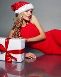 Sexy blonde Sankt in einem roten Kleid, das Weihnachtsgeschenk hält Lizenzfreie Stockbilder