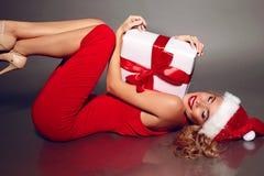Sexy blonde Sankt in einem roten Kleid, das Weihnachtsgeschenk hält Stockbild
