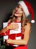 Sexy blonde Sankt halten vorhanden nahe dem Weihnachtsbaum Lizenzfreies Stockbild