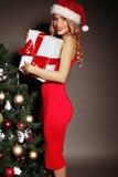 Sexy blonde Sankt halten vorhanden nahe dem Weihnachtsbaum Lizenzfreies Stockfoto