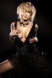 Sexy blonde Schönheit, die im eleganten schwarzen Kleid sitzt Stockbild
