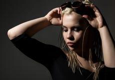 Sexy blonde Schönheit mit Dreadlocks auf einem dunklen Hintergrund im Studio Lizenzfreie Stockfotografie
