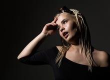 Sexy blonde Schönheit mit Dreadlocks auf einem dunklen Hintergrund im Studio Stockfotografie