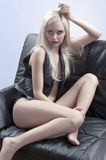 Sexy blonde sitting on a sofa Royalty Free Stock Photo