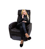 Sexy blonde talking on the phone. Sitting on the couch with her legs crossed. White background Royalty Free Stock Photography