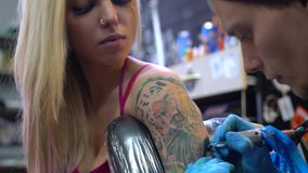 Sexy blonde and tattoo master at work in studio stock video
