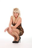 Sexy blonde vrouw crouches neer in korte kleding Royalty-vrije Stock Foto's