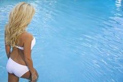 Sexy Blonde Vrouw die in Bikini in Blauwe Pool loopt Stock Afbeelding