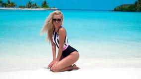 Sexy blonde Vrouw in het modieuze bikini suntanning op tropisch strand Vrij het slanke meisje stellen op exotisch eiland door moo stock foto