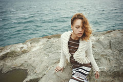 Sexy blonde wearing dress with stripes and cardigan posing on rock in the sea Stock Image