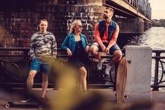 Sexy blonde weibliche und zwei zufällige Männer mit dem langen Brett, das nahe Wasserkanal in der Stadt aufwirft Stockfotografie