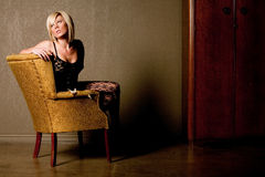 Sexy blonde woman. On antique chair Royalty Free Stock Image