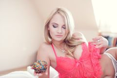 blonde woman in bed holding doughnut Royalty Free Stock Image